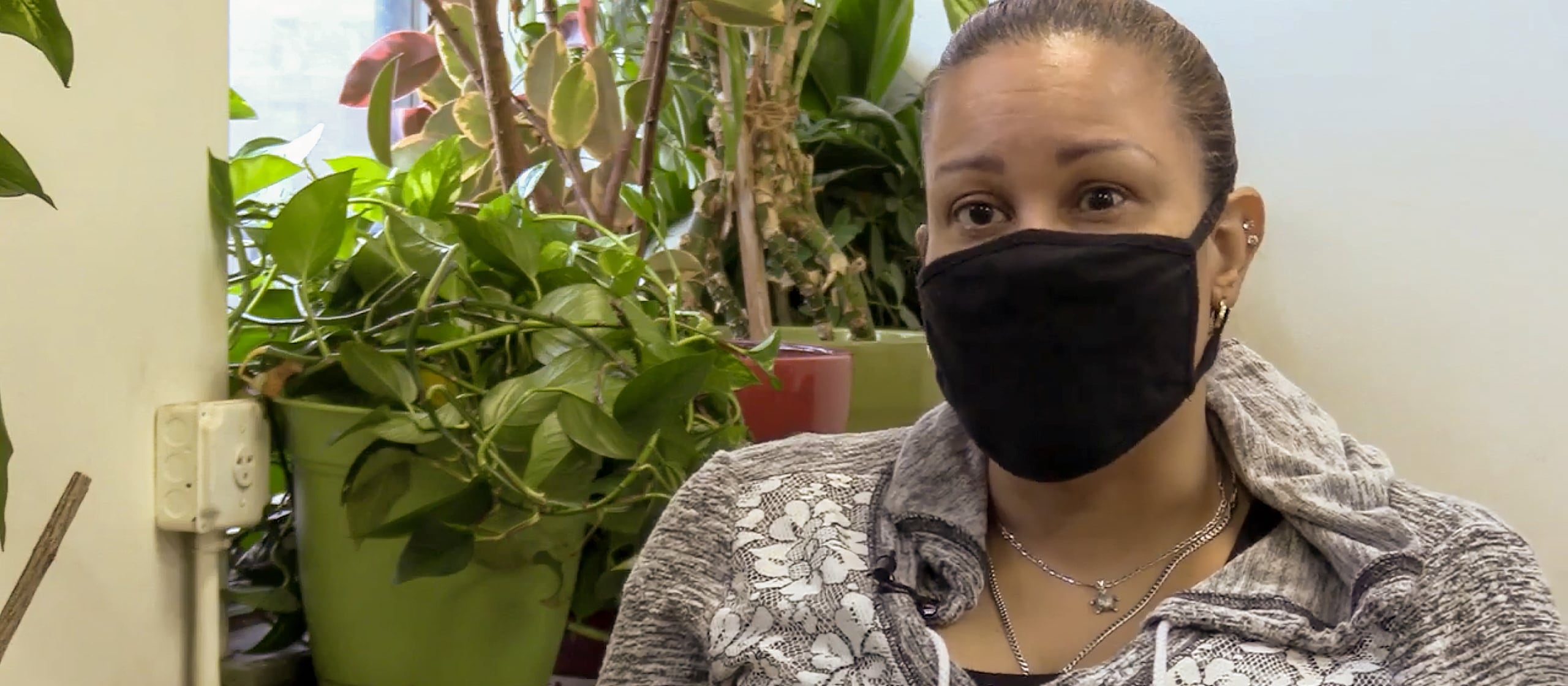 A woman looking into the camera with a black mask on.