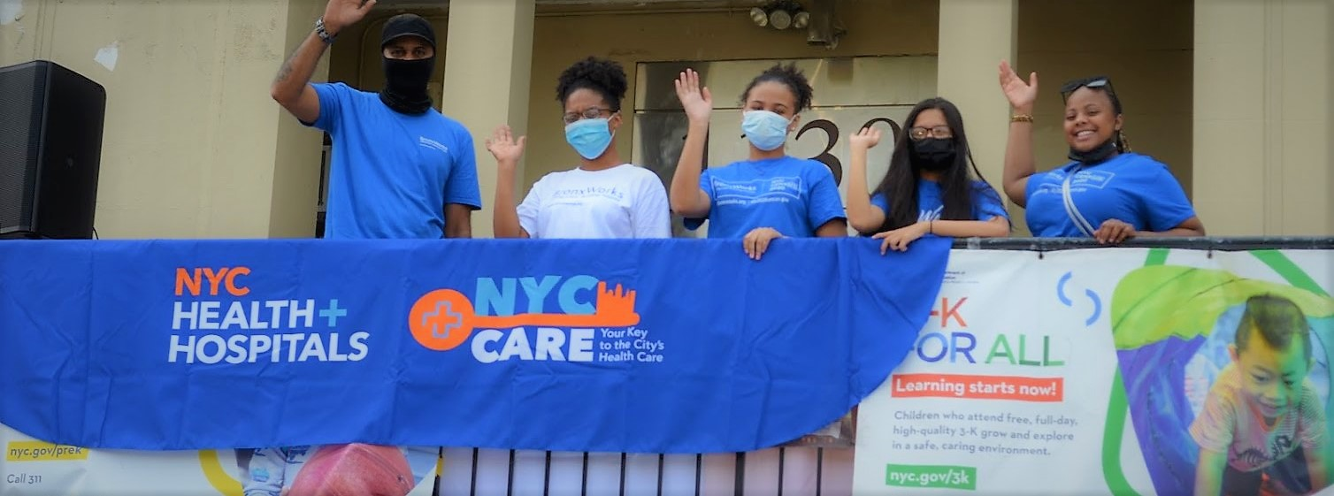 Five people stand behind an NYC Care banner, waving at the camera and wearing masks.