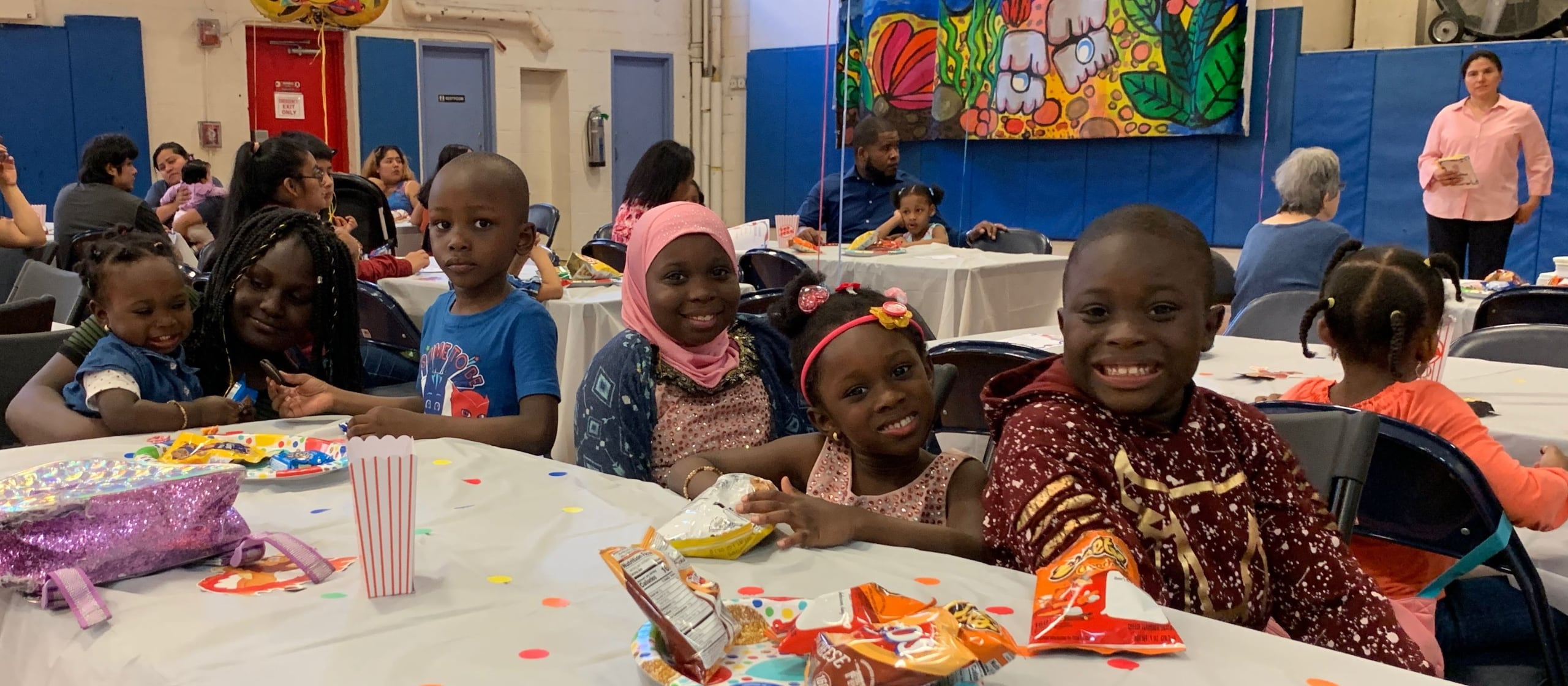 A group of children smiling looking at the camera while eating snacks