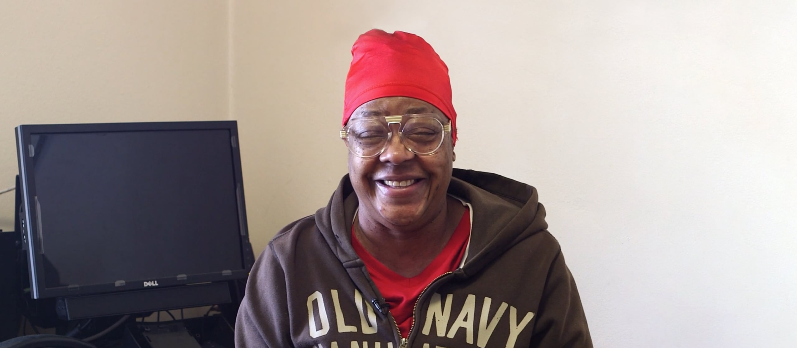 A person with glasses smiling from the seniors homelessness prevention project