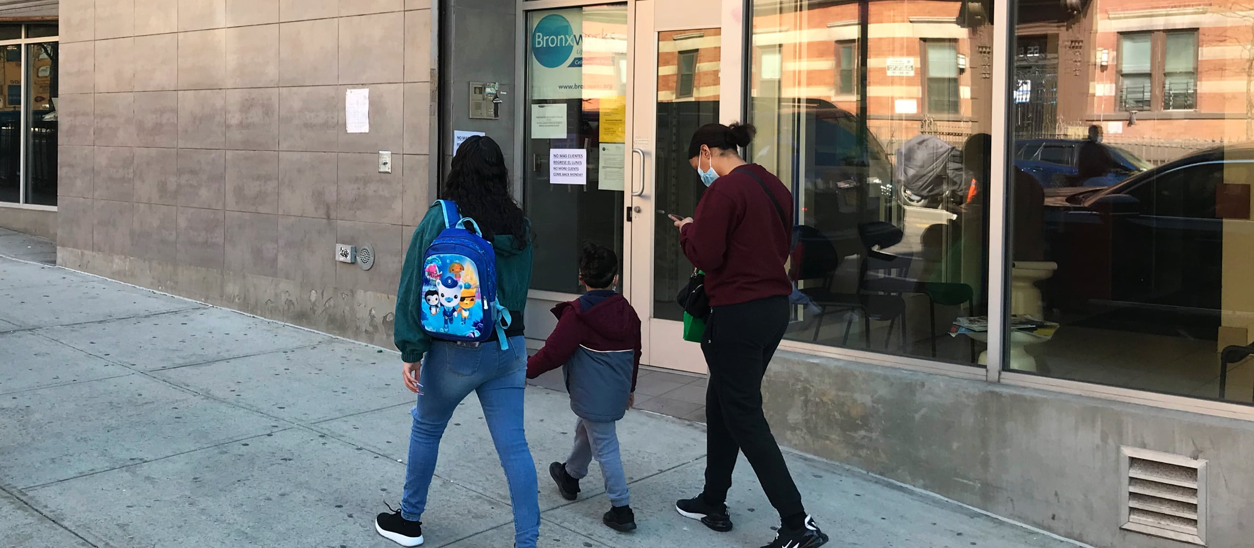 Two people talking down the street with a kid in the middle while passing a BronxWorks office