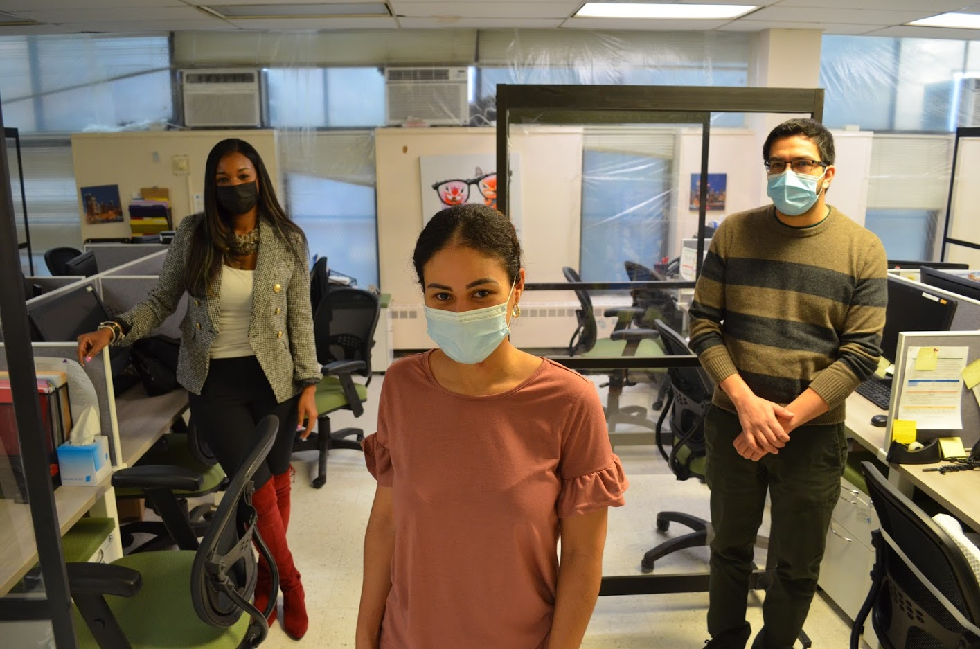 Three people standing in the middle of a office space in a triangle form looking at the camera with their masks on. The one in the middle is a women, the one on the top left of the photo is a women and the one on the top right of the image is a male