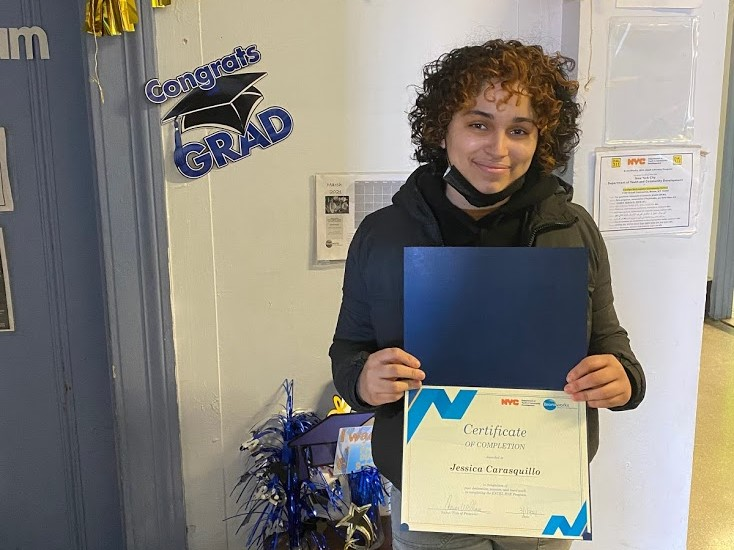 A person holds a certificate commemorating graduation from a high-school equivalency program.