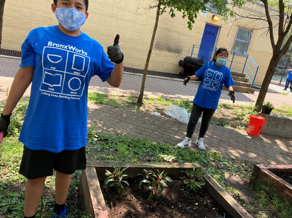 A students gives a thumbs-up while standing with another student near a garden bed