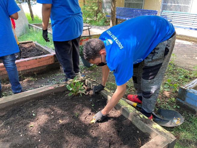 A teenage boy in a blue BronxWorks shirt bends over a garden, planting a seed. Other children in blue shirts work in the background.