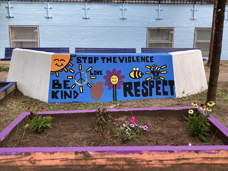 """A painted mural on a short wall. The mural reads """"Stop the Violence"""", """"Be Kind"""", and """"respect"""" There are paintings of a sun, a flower, a peace symbol, and a bee."""