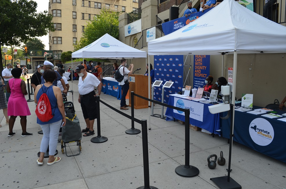 Multiple boohs set up on the sidewalk in front of the BronxWorks Community Center providing program information to people walking by.