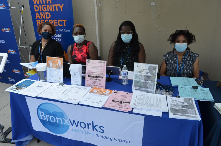 Four people sit behind a table with multiple paper flyer. The BronxWorks logo hangs in front of the table.