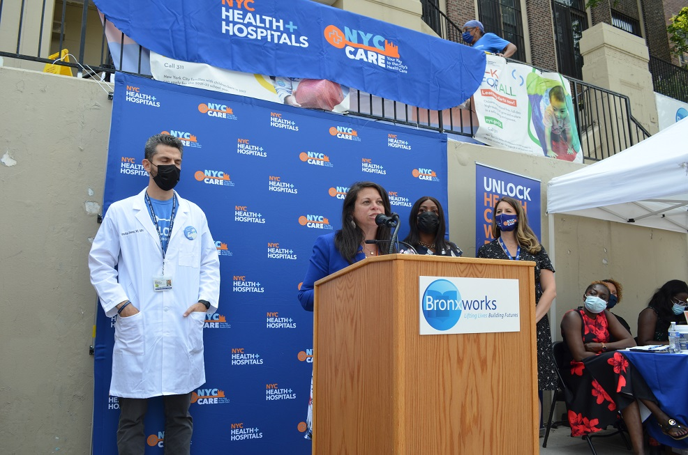 Eileen torres stands at a podium with the Bronxorks Logo, speaking to a crowd. She is flanked by a few people with NYC Care signs behind her.