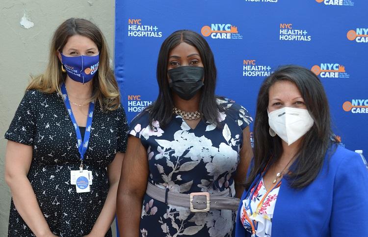 Thre women standing next to each other wear masks
