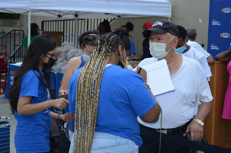 NYC Care Outreach workers taking down information of people waiting in line to enroll them in NYC Care