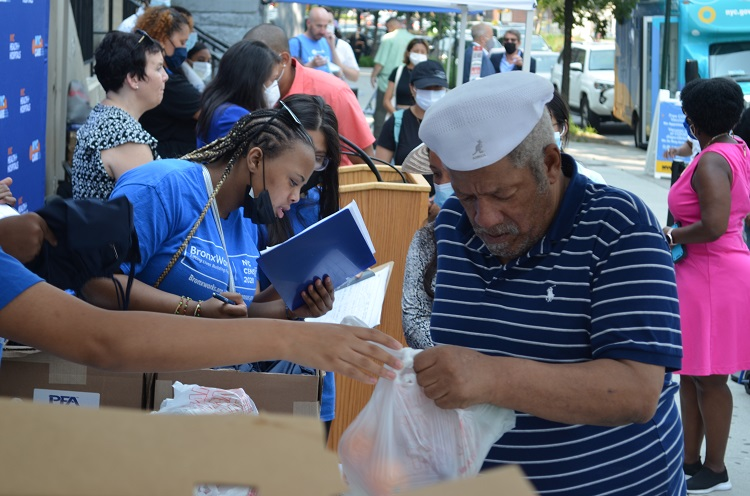 A man wearing a hat takes abag of food from a Bronxworks employee. Boxes of bags and bread, as well as more plastic bags of food, sit on the table between them.